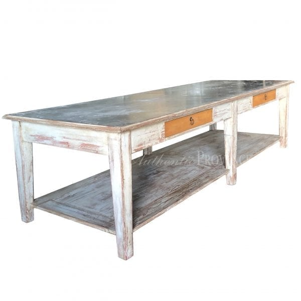 Side view of a large rectangular table with rustic metal top and wooden base with two faux drawers and bottom shelf