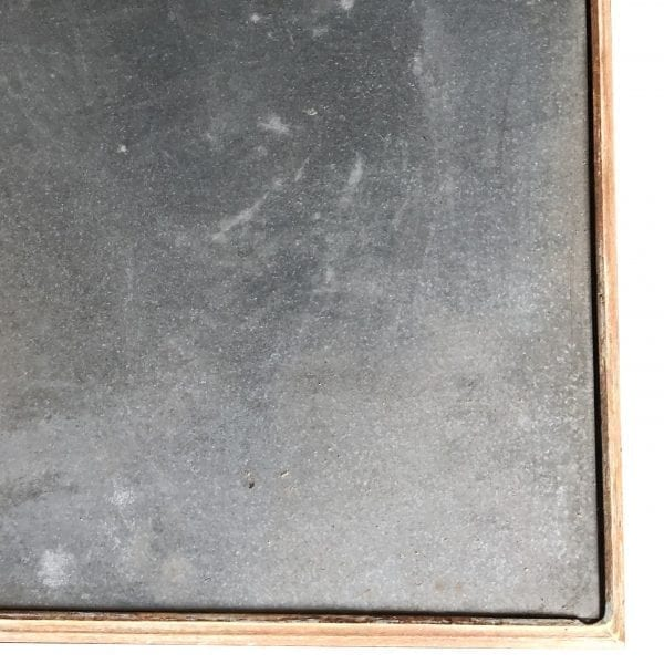 Close up of the corner of a large rectangular table with rustic galvanized metal top