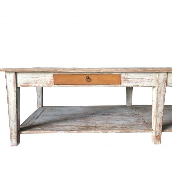 Close up of a large rectangular table with wooden base and two faux drawers and bottom shelf