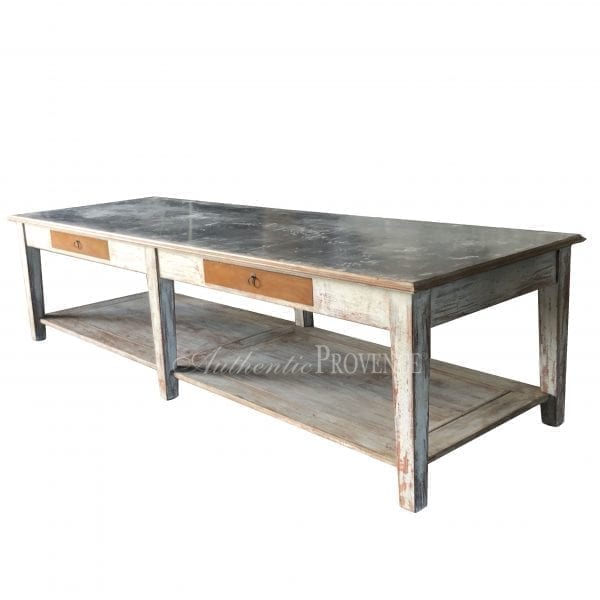 A large rectangular table with rustic metal top and wooden base with two faux drawers and bottom shelf