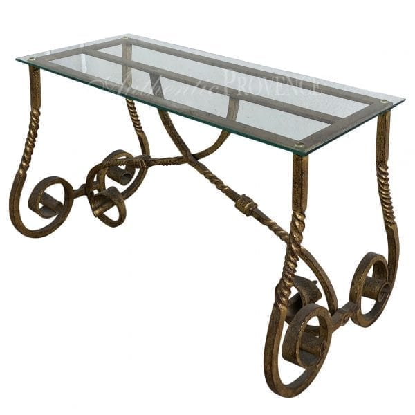 Side view of a 1940's side table with a rectangular glass top and a gilded metal base with scrolls