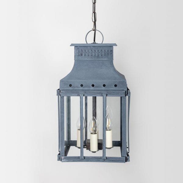 Historical French carriage lantern with four lights surrounded by vertical bars.