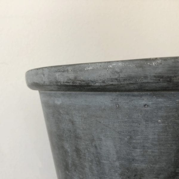 Close up of the rim of a small metal planter with rim