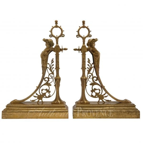 Set of elegantly worked andirons in gilded bronze adorned with acorns, scrolls and foliage on a decorated base