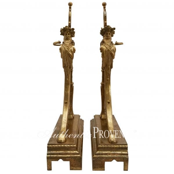 Front view of elegantly worked andirons in gilded bronze adorned with acorns, scrolls and foliage