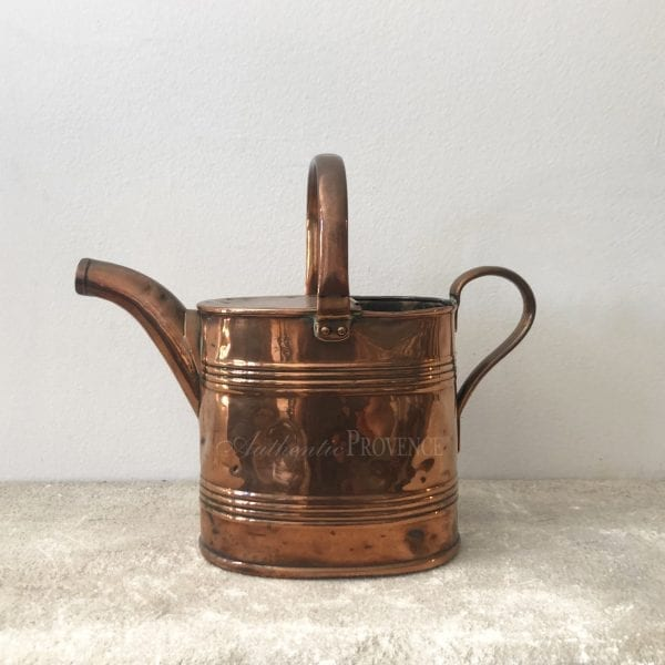 A large antique French watering can in copper
