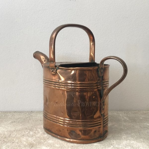 Side view of a large antique French copper watering can