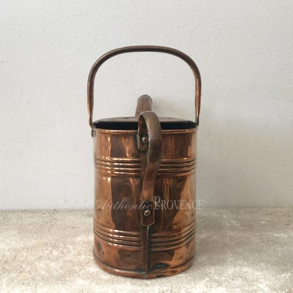 Back view of a large antique French watering can in copper.