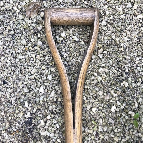 Close up of the wooden handle of a antique English hayfork