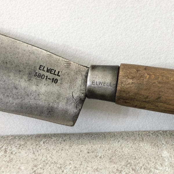 Close up of an antique billhook garden tool with a wooden handle