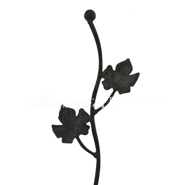 Close up of a tall decorative garden stake from England with leaf ornaments in galvanized metal
