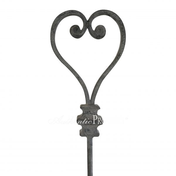 Close up of a tall decorative garden stake with a heart shaped ornament in galvanized metal