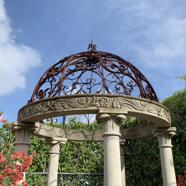 Close up of the top of a charming 20th century garden gazebo with five columns and wrought iron pierced dome