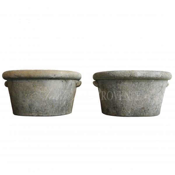 """A pair of very rare French """"ponne en pierre"""" hand carved limestone planters of oval shape and topped with a wide rim."""