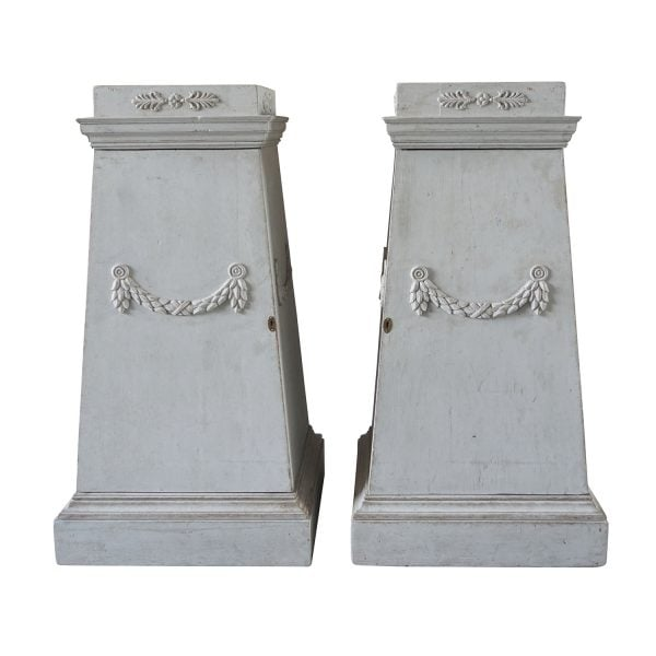 A pair of Gustavian pedestals made of light grey painted Pinewood with carved garlands. Circa 1790, Sweden, Scandinavia.