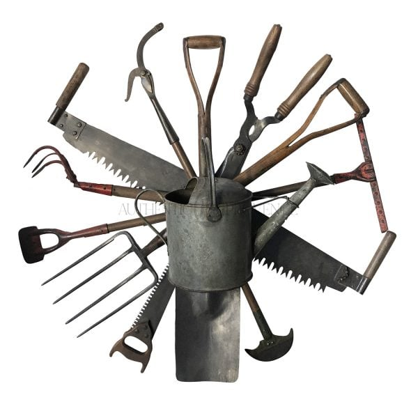 A playful wall mount antique tool wreath composed of a collection of late 19th Century English garden tools with a centered watering can