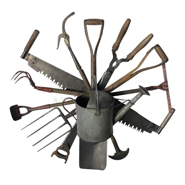 A wall mount antique tool wreath composed of a collection of late 19th Century English garden tools with a centered watering can