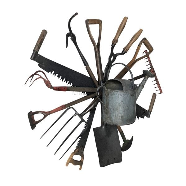 Side view of a wall mount antique tool wreath composed of late 19th Century English garden tools with a centered watering can
