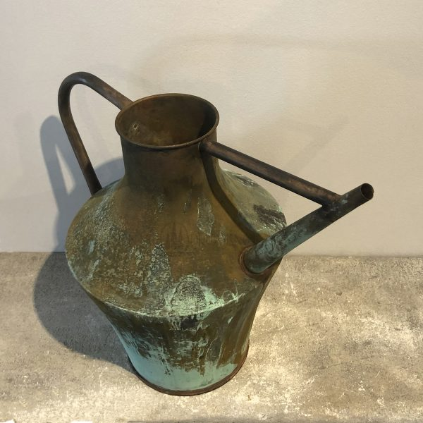 Overhead view of a large amphora shaped copper watering can with a natural antique patina