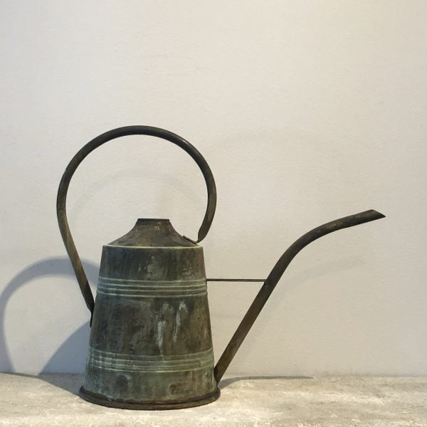 A large conical antique watering can in copper from France with a top handle and curved spout.