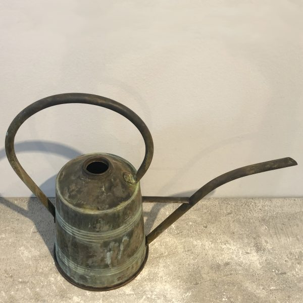 Overhead view of a large conical antique watering can in copper with a top handle and curved spout.