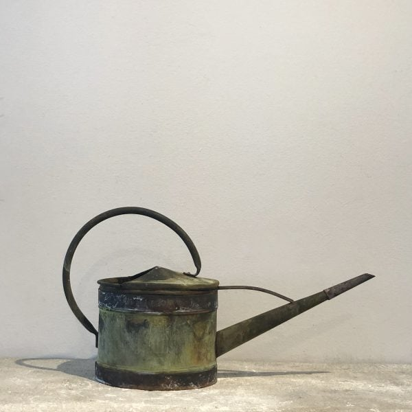 A small antique watering can with a narrow spout in copper with a natural antique patina