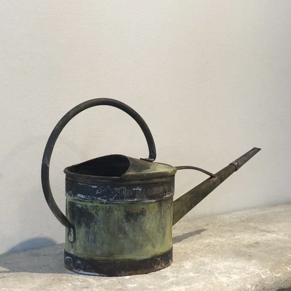 Back view of a small 19th century copper watering can with a narrow spout and a natural antique patin