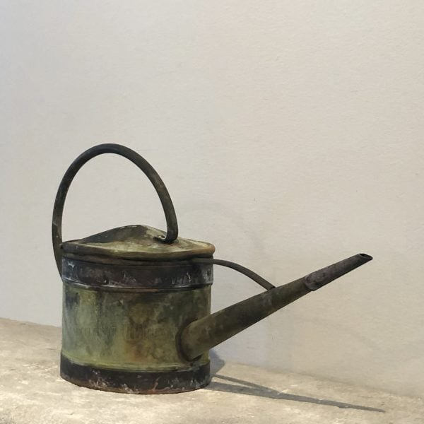 A small 19th century watering can with a narrow spout in copper with a natural antique patina