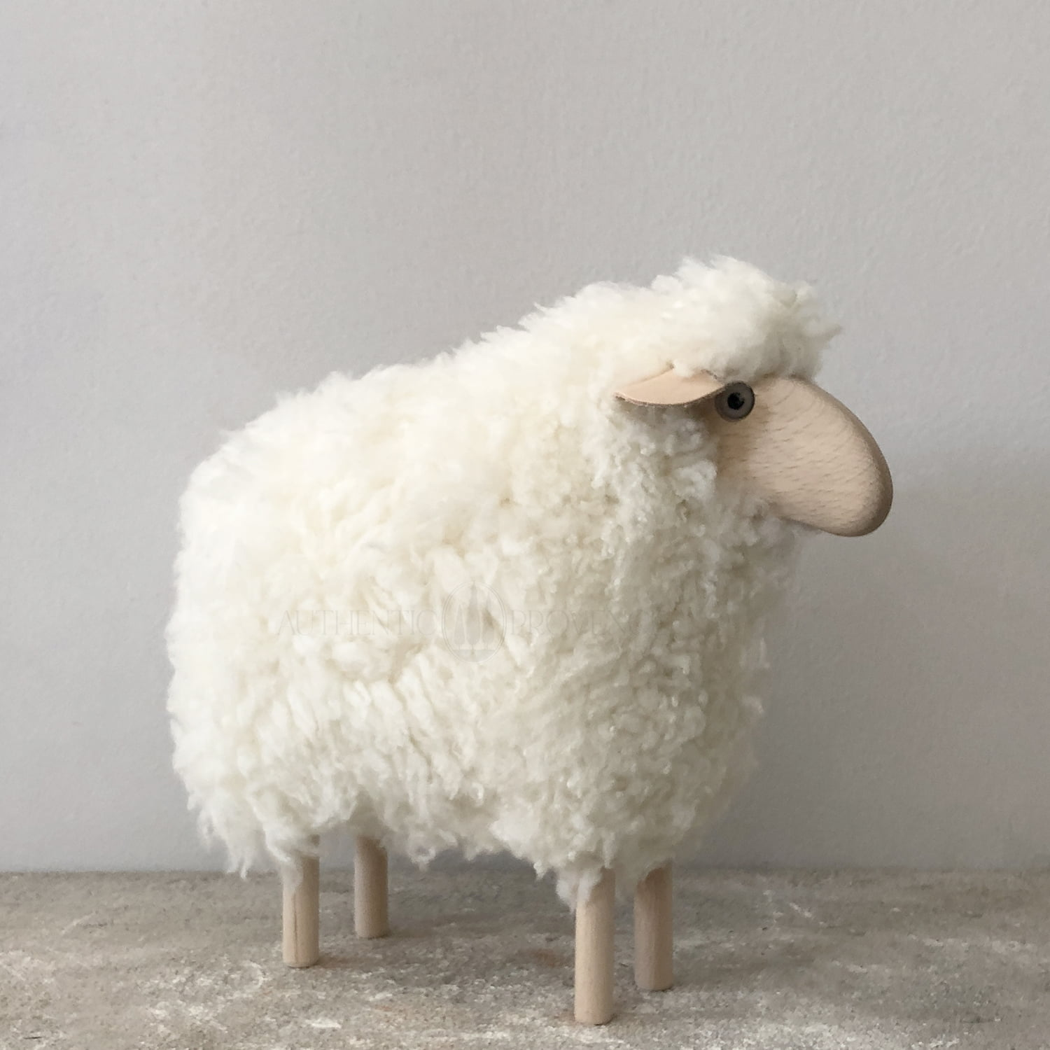 An extra small sheep hand crafted with a glass eyes, sheepskin fur body, wooden legs and snout with light colored genuine leather ears.